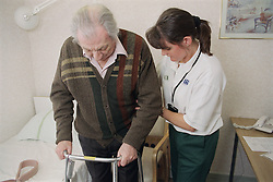 Female occupational therapist showing elderly man how to use a frame and leg lifter to build up strength in his legs,
