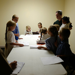 Young girls and boys of the Mennonite faith sit around a table with coloring books as Kathy Kauffman, right, holding 15 month-old Holly keeps a watchful eye in a small room as the adults attend a evening church service and meeting at the Mennonites Cuba Christian Brotherhood Church, a small building adjacent to the 5-Star Building in Cuba, Missouri on Wednesday, Sept. 28, 2016. (Photo by Keith Birmingham Photography)