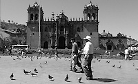 People walking in the square in front of the Cathedral of Santo Domingo in Cusco, Peru