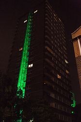 """London, UK. 14th June, 2018. The Green for Grenfell illuminations are lit at the Grenfell Tower and the twelve closest tower blocks (seen here Whitstable House on the Silchester East Estate) on the first anniversary of the fire in a display intended to 'shine a light"""" of love and solidarity for all those affected and to raise awareness of the plight of those still without new homes after one year. Green for Grenfell is a community-led initiative in collaboration with tenants' and residents' associations and Grenfell United."""