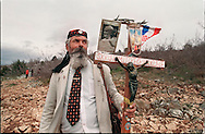 MEDJUGORJE, BOSNIA-HERCEGOVINA:  A Bosnian Croat man holds a crucifix while making his way up the hill of Podbrdo of Mount Crnica, now called Apparition Hill, near Medjugorje. The site, visited by millions of pilgrims, is where 6 children claimed to have first been visited by the Virgin Mary in 1981.  (Photo by Robert Falcetti). .