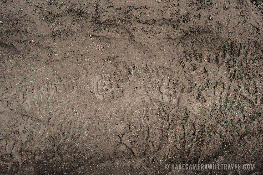 Hikers' boot prints marked clearly in the thick brown dirt of the Mt Kilimanjaro's Lemosho Route.
