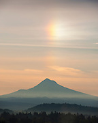 Sun dog over Mount Hood, Portland, Oregon.  Also known as a Mock Sun or Parhelia, this is a halo phenomenon observed at 22-degrees offset from the sun (the sun is out of frame to the left).  They are formed in cold conditions when the air contains sufficient plate ice crystals floating horizontally like leaves.  An uncommon occurrence in Portland.