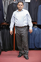 Full length portrait of male tailor standing in menswear store