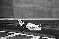 Homeless man sleeping under newspapers, beneath empty billboards, in Shinjuku,. Tokyo, Japan.