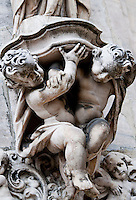 Milan, Italy, Duomo Cathedral - 2 cherubs supporting a stone pillar.