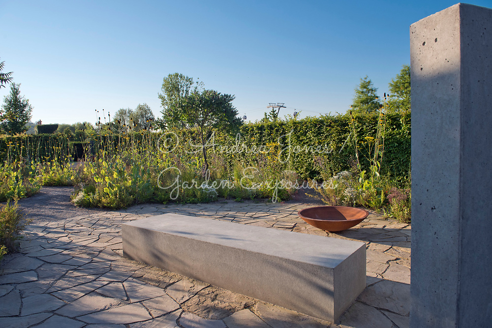 Concrete wall and bed represents a house, rusted iron bowl represents furniture whilst the stone paving is the floor of a previous house. <br /> <br /> Carpinus betulus (hornbeam) hedge with border including Rhus typhina (Stag's horn sumach), Rudbeckia maxima (great coneflower), Anaphalis triplinervis, Patrinia scabiosifolia (Golden valerian, Golden lace) and Anaphalis triplinervis in background.<br /> <br /> IGA Berlin 2017, 'The Garden of Vulcan'<br /> Design: Tom Stuart-Smith Ltd