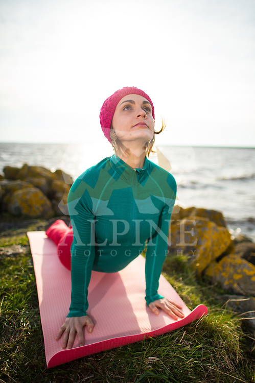 A female athlete as seen performing yoga at the coast of North Sea on a sunny Spring afternnon.