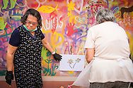 08/09/2015 - Lisbon, Portugal: Aida Alves, 76, looking for a colour to paint her flowers on the wall of Lata 65 workshop. Lata 65 was project created by Lara Seixo Rodrigues and is a creative workshop teaching street art to senior citizens. (Eduardo Leal)