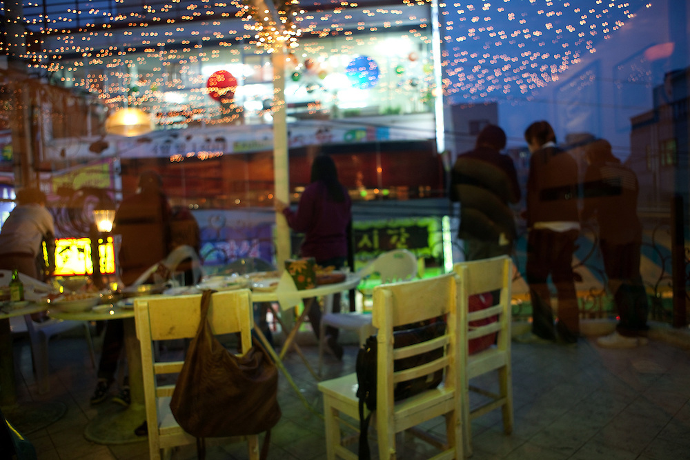 Studenten der Chung-Ang Universitaet in Anseong - ung. 80 Km von Seoul gelegen - treffen sich auf der Terasse einer Kneipe in einem Stadtviertel welches an den Campus angrenzt. <br /> <br /> Students of the  Chung-Ang University - located in Anseong about 80 Km from Seoul - are meeting on a terrace of a pub in a quater close to the campus.