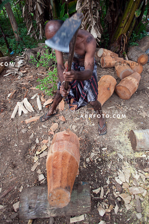 Craftsmen axes away on a large piece of wood in this case 'jak' or Artocarpus Integrifolia which is later hollowed out & carved to be used as a drum.