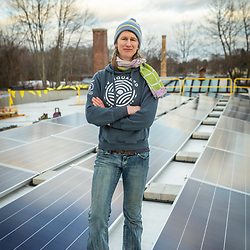 PV Squared employee Maya Fulford at a solar panel installation on the roof of a commercial building in Greenfield, Massachusetts.