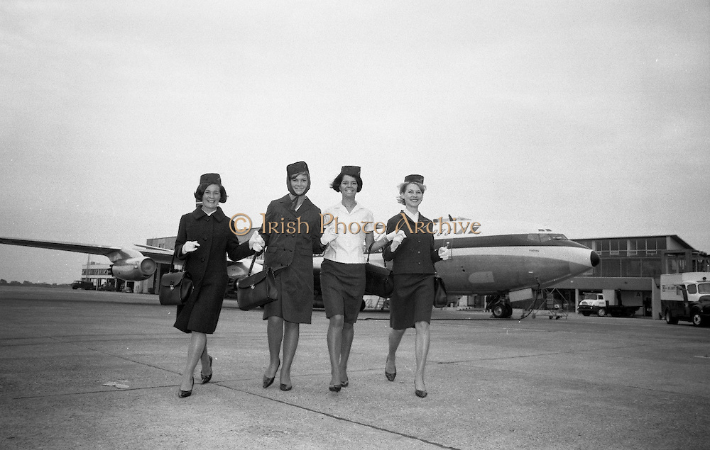 A new uniform for Aer Lingus Hostesses was introduced at Dublin Airport. .The new uniform, designed by Irene Gilbert, consists of a two-piece suit in ivy-green lightweight tweed, a matching top-coat in a heavier tweed, a shower-proof coat with a matching head-piece and a forage style hat. The skirt is approximately 1 to 1 1/2 inches above the knee.  Picture shows Aer Lingus Hostesses Imelda Grant, Eileen Malone, Eilish O'Connor and Goderic Abele showing the various ways of wearing the new uniform..15.06.1966