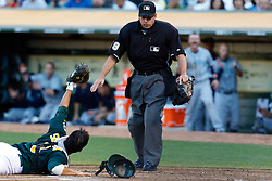 July 5, 2011; Oakland, CA, USA;  Oakland Athletics catcher Kurt Suzuki (8) appeals to MLB umpire Andy Fletcher (49) after missing a tag on Seattle Mariners second baseman Dustin Ackley (not pictured) at home plate during the second inning at O.co Coliseum.