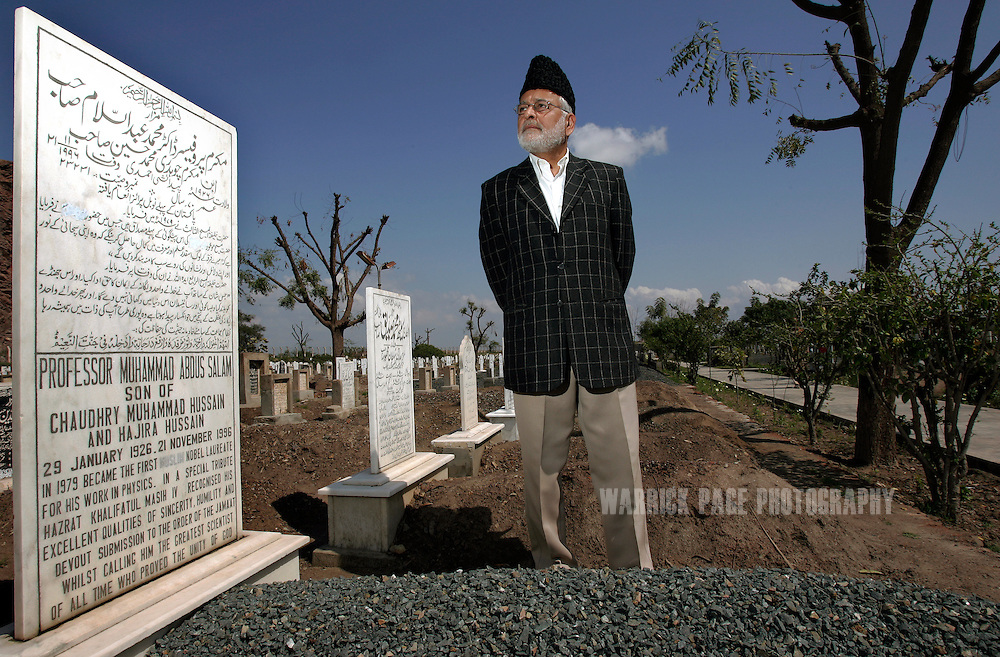 RABWAH, PAKISTAN - MARCH 13: Rabwah community leader, Shameem Ahmad Khalid stands next to the grave site of the first Muslim Nobel Laureate, Prof Muhammed Abdus Salam, in the Bihishti Maqbra (graveyard), March 13, 2007, Rabwah, Pakistan. The Islamic splinter group's  community was forced by the government to remove all Muslim and Koranic references from the Nobel laureate's grave and those of all other Ahmadi's buried in the cemetery, or face prosecution. The town of Rabwah and it's Ahmadi population of 50,000 have been under criminal investigation for the past 20 years for impersonating Muslims. Numerous people serving lengthy jail terms under Pakistan's anti-blasphemy laws and a 1974 constitutional amendment that deemed Ahmadi's as non-Muslim. The town of Rabwah has been subjected to numerous attacks and frequent persecution by sectarian terrorist groups. (Photo by Warrick Page)