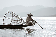 Local fisherman relaxing on his boat in the evening light on Lake Inle, Myanmar