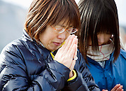 A mother and daughter weep as the siren is sounded to mark the one year anniversary of last year's magnitude 9 earthquake and tsunamis during a remembrance service in Ofunato City, Iwate Prefecture, Japan on 11 Mar. 2012. .Photographer: Robert Gilhooly