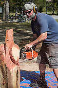 Chad Townson carves a piece of cypress wood into a fleur de lis with a chain saw at the Abita Springs Water Festival on October 16, 2016