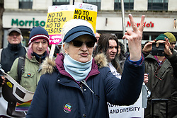 "© Licensed to London News Pictures . 09/02/2019. Manchester , UK . A stand up to racism supporter sticks two fingers up to a "" Yellow Vest "" protest in Piccadilly Gardens in Manchester City Centre . The yellow vest concept has been adopted from French demonstrators by some British groups in support of Brexit , Donald Trump and former EDL leader Stephen Yaxley-Lennon - aka Tommy Robinson . A similar demonstration in the city in January was ridiculed after protesters were kettled by police in front of a branch of Greggs the Baker . Photo credit : Joel Goodman/LNP"