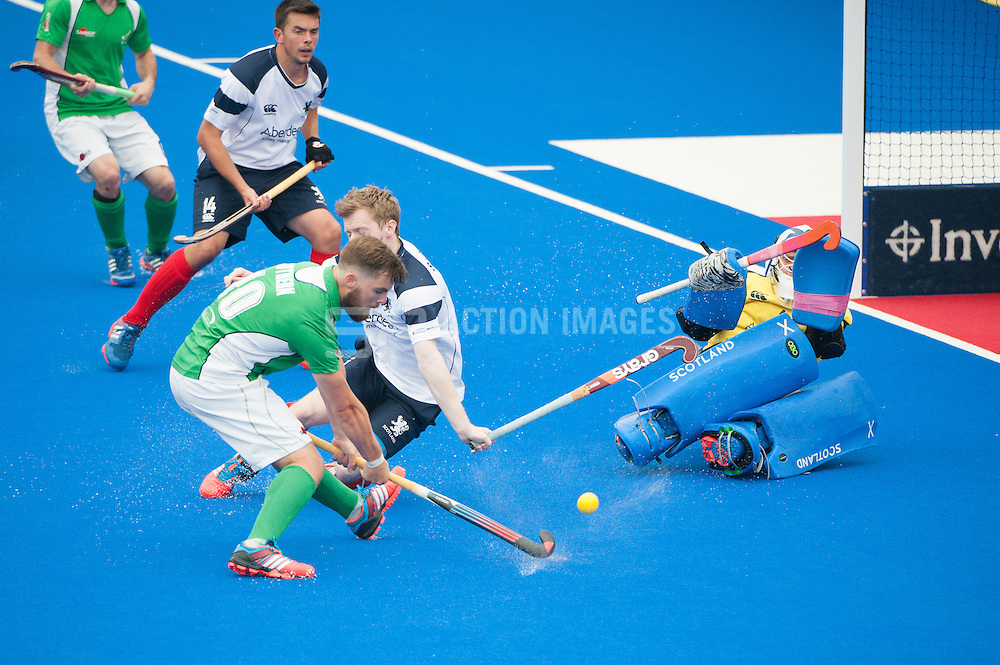 Alan Sothern (IRE) shoots while Scottish goalkeeper Jamie Cachia (SCO) takes evasive action. Ireland v Scotland - Investec London Cup, Lee Valley Hockey & Tennis Centre, London, UK on 10 July 2014. Photo: Simon Parker