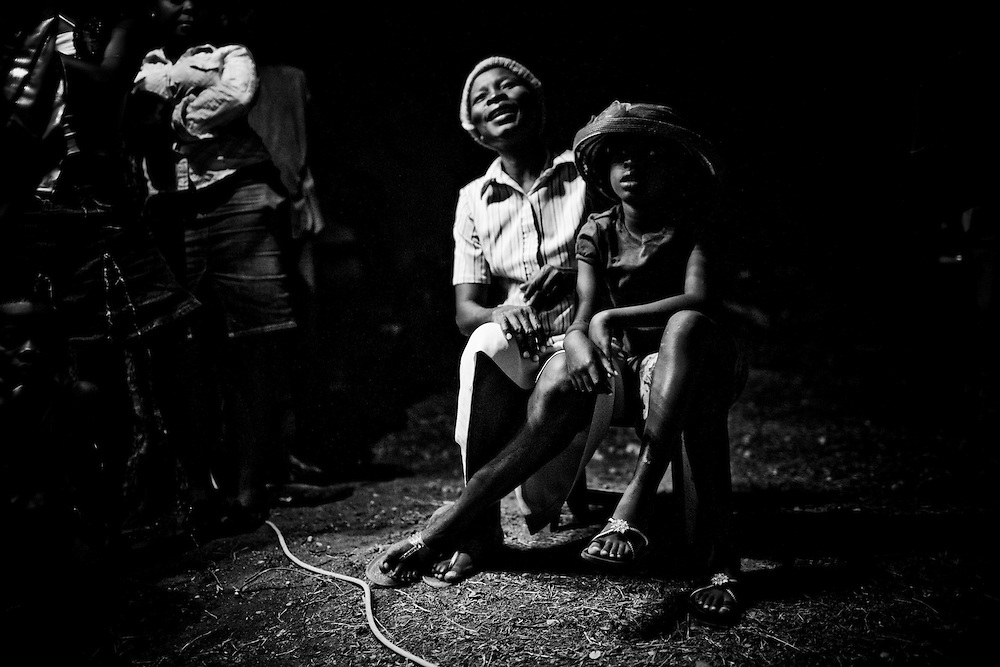 Two people share a chair while waiting for an outdoor evening church service to begin at a camp for those displaced by the recent earthquake in Petionville, outside Port-au-Prince, Haiti.