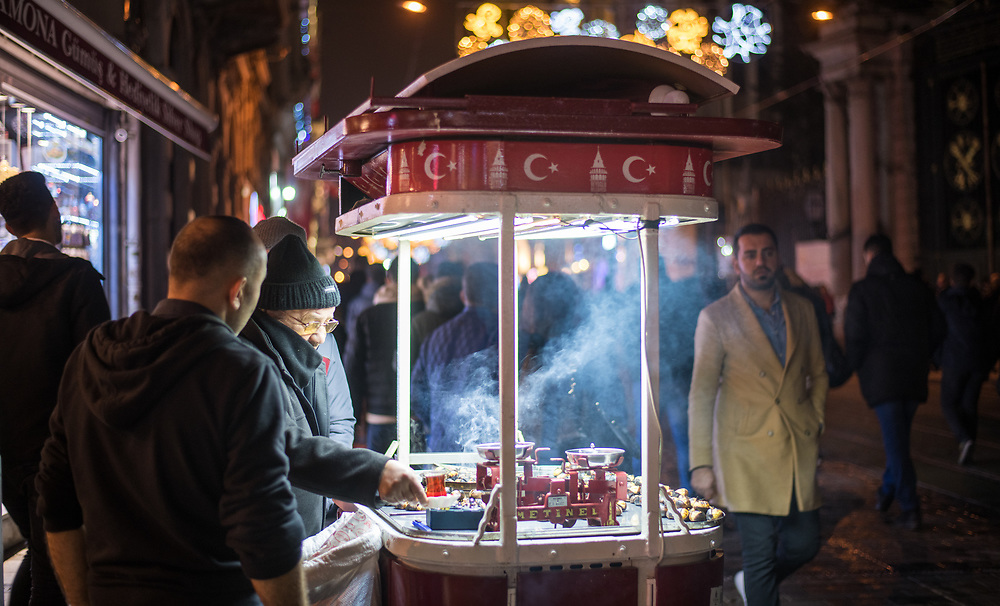 Street vendor roasts chestnuts at food cart for customer with steam rising, Istanbul, Turkey