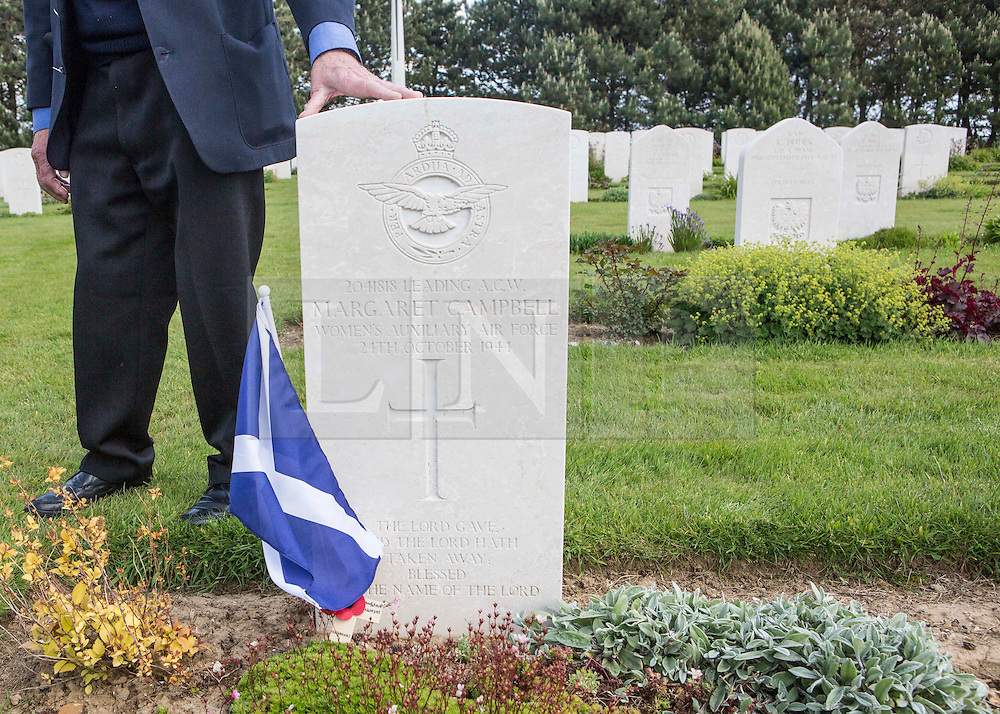 © Licensed to London News Pictures. 29/05/2014. Alan Hartley places a hand on the grave stone of Margaret Campbell, one of the many nurses who flew several missions bringing injured soldiers back to the UK.  Known as the Flying Nightingales the nurses flew with the RAF crew and were not allowed to wear a parachute as their sole responsibility was the casualty.  If the plane crashed, the nurses were ordered to stay with the casualties at all costs.  Photo credit : Alison Baskerville/LNP