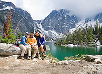 Two adult couples posing for a group portrait at Colchuck Lake in the Cascades of Washington, USA.