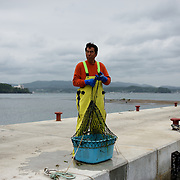 May 29, 2013 - Togura, Japan: A fisherman collects a fish box from the waters beside a pier in Togura, Miyagi prefecture. Since the 2011's tsunami that struck over the coastal areas of Japan, the fishing community of Togura, devastated by the natural disaster, formed a cooperative where all the families work together using the only two remaining boats in the whole village. (Paulo Nunes dos Santos)