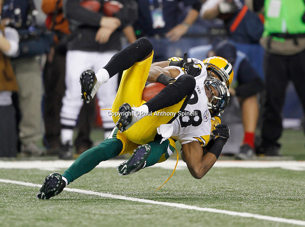 Pittsburgh Steelers wide receiver Emmanuel Sanders (88) catches a second quarter pass good for a first down while getting slammed to the turf by Green Bay Packers cornerback Tramon Williams (38) during Super Bowl XLV against the Green Bay Packers on Sunday, February 6, 2011, in Arlington, Texas. The Packers won the game 31-25. ©Paul Anthony Spinelli