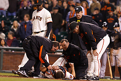 May 25, 2011; San Francisco, CA, USA;  San Francisco Giants catcher Buster Posey (bottom, center) is attended to by medical staff while relief pitcher Guillermo Mota (back, left), manager Bruce Bochy (right) and umpire Joe West (back, center) watch during the twelfth inning against the Florida Marlins at AT&T Park. Posey was injured after a collision with Florida Marlins center fielder Scott Cousins (not pictured) at home plate.  Florida defeated San Francisco 7-6 in 12 innings.