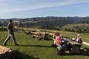 A young Pole brings a beer to the table with friends enjoying mountain views across the valley, on 21st September 2019, in Jaworki, near Szczawnica, Malopolska, Poland.