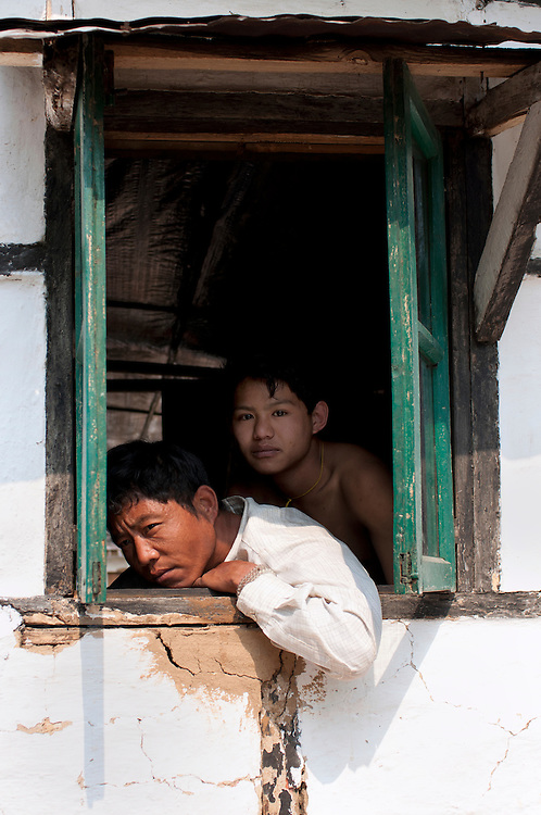 In a remote, impoverished agricultural village in India, a man and boy gaze out from a window of their home.