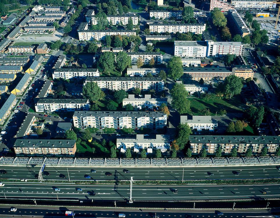 Nederland, Zuid-Holland, Dordrecht, 17-10-2003; de autosnelweg A16 (Rotterdam -Breda) loopt direct langs de woonwijk 'Wielwijk'; om geluidsoverlast tegen te gaan is een enorm, half gebogen, geluidsscherm gebouwd ( met gebogen betonnen spanten en glazen dak); de jaren zestig woonwijk is gedeeltelijk gesloopt / gerenoveerd; stadsvernieuwing, naoorlogse wijken, flats, milieu, geluidswal, verkeer en vervoer,volksgezondheid.<br /> Foto Siebe Swart