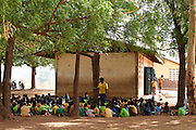 A volunteer teacher takes a large class of infants from the kindergarten Wungu School under a tree. They are learning their alphabet. If it weren.t for the volunteer teacher leading the class this would not be happening.