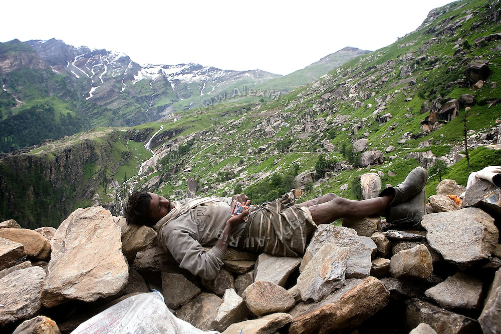 A labourer taking a break on a bed of stones against a view of the mountain landscape along the Leh-Manali Highway.