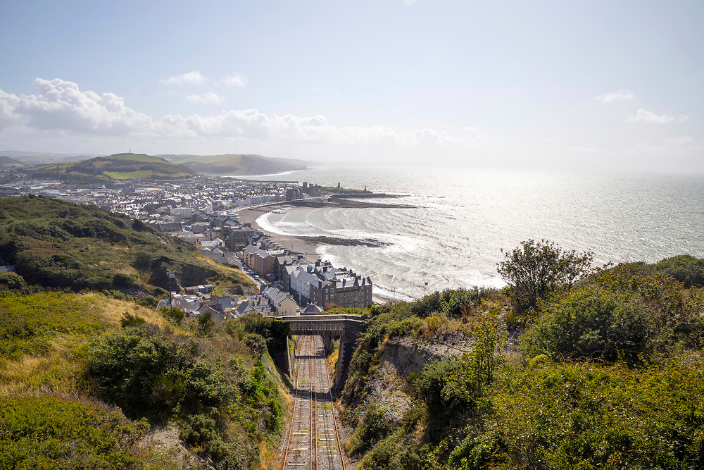 ABERYSTWYTH, WALES, UK 18TH AUGUST 2019 - View over Aberystwyth town and Ceredigion coastline with Aberystwyth Cliff Railway tracks - the longest fenicular railway in Great Britain. Taken from top of Constitution Hill, Aberystwyth, Mid Wales, Britain.