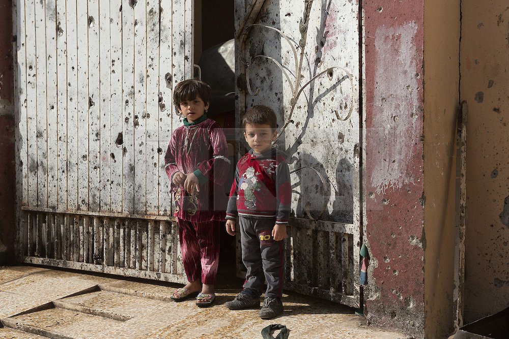 Licensed to London News Pictures. 11/11/2016. Mosul, Iraq. Two Iraqi children stand in front of their home's bullet riddled gate in Mosul's Al Intisar district on the south east of the city. The Al Intisar district was taken four days ago by Iraqi Security Forces (ISF) and, despite its proximity to ongoing fighting between ISF and ISIS militants, many residents still live in the settlement without regular power and water and with dwindling food supplies.<br /> <br /> The battle to retake Mosul, which fell June 2014, started on the 16th of October 2016 with Iraqi Security Forces eventually reaching the city on the 1st of November. Since then elements of the Iraq Army and Police have succeeded in pushing into the city and retaking several neighbourhoods allowing civilians living there to be evacuated - though many more remain trapped within Mosul.  Photo credit: Matt Cetti-Roberts/LNP
