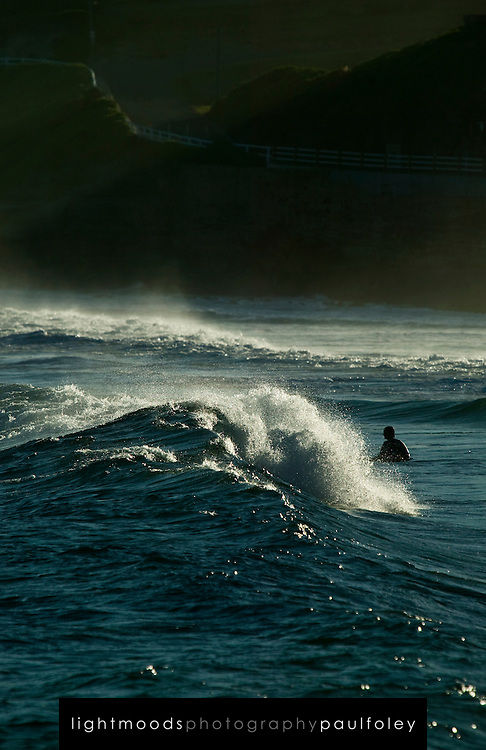 Compressed views of body surfers at an Australian Beach in the late afternoon sun.
