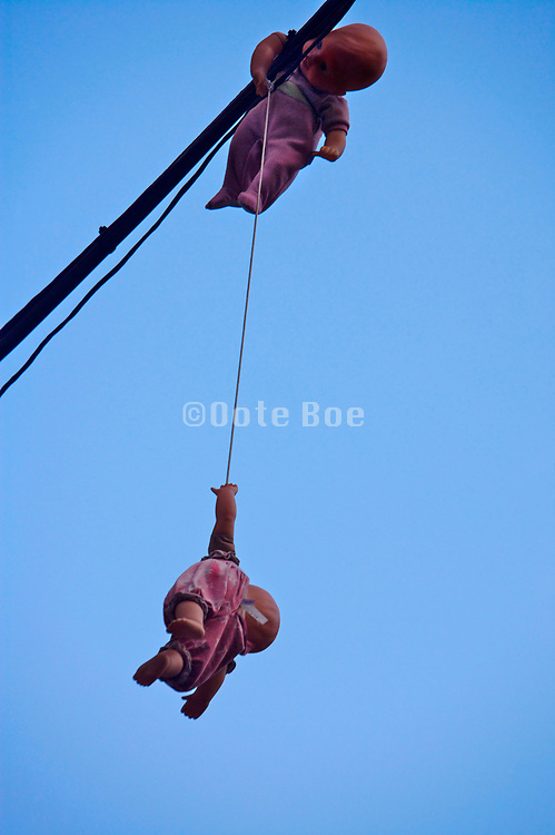 dolls hanging from power line