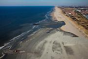 Nederland, Zuid-Holland, Monster, 18-03-2009; Versterking van de kust van Delfland tussen Ter Heijde en 's-Gravenzande door middel van zandsuppletie. Het strand onder in beeld is breder, hier is al gesuppleerd. Meer naar boven, naar het Noordoosten richting Den Haag, moet er nog zand opgespoten worden. In het midden - de donkere plek - is suppletie in volle gang. De kust bij Ter Heijde, het dorpje rechtsboven in beeld, direkt achter de duinen en met rode daken, is bekend als een van de 'zwakke schakels'. Dit vanwege de geringe breedte van de duinen. Rechts van Ter Heijde Monster en kassen van het Westland. De strekdammen in zee zijn de Delflandse Hoofden. .The coast of Delfland, between Hoek van Holland and The Hague, is being strengthened by means of sand-supplementation. The beach in the lower part of the picture is wider, sand has already been supplemented. More to the Northeast (top of picture), sand still needs to be sprayed onto the beach. In the middle (the dark area) sand-supplementation is in progress. The coast at Ter Heijde (red-roofed village behind the dunes) is a so-called 'weak-link' because of the weakness of the dunes..Swart collectie, luchtfoto (toeslag); Swart Collection, aerial photo (additional fee required); .foto Siebe Swart / photo Siebe Swart