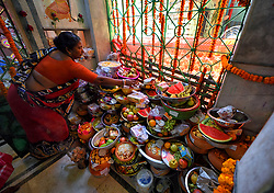 March 28, 2019 - Kolkata, WEST BENGAL, India - A woman seen preparing the offering of Sheetala puja at the Temple in Kolkata ..As per Hindu mythology Devi sheetala is being worshipped as she cures smallpox's, sores, ghouls, pustules and diseases. Hence Hindu people observe Fast for the whole day and doing different traditional practices like Dandi (Lying on Ground) and put burning Fire Pot on their heads while worshiping to Devi sheetala for betterment of their family members. (Credit Image: © Avishek Das/SOPA Images via ZUMA Wire)