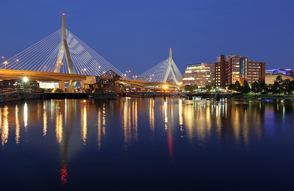 The Leonard P. Zakim Bunker Hill Memorial Bridge is a cable-stayed bridge across the Charles River in Boston, Massachusetts. This photography image shows the Zakim Bridge, Spaulding Rehabilitation Hospital, TD Bank North Garden, North Station, and their reflections at twilight as seen from the Paul Revere Park in Boston. Leonard Zakim was a civil rights leader. The Zakim bridge  was built as part of the Boston's Big Dig and it represents the worlds widest cable-stayed bridge.<br />