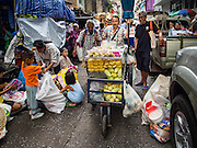 30 AUGUST 2016 - BANGKOK, THAILAND:   A fruit vendor pushes his cart through the crowd of people who got food and clothing from the Poh Teck Tung Shrine on the last day of Hungry Ghost Month in Bangkok. Chinese temples and shrines in the Thai capital host food distribution events during Hungry Ghost Month, during the 7th lunar month, which is usually August in the Gregorian calendar.        PHOTO BY JACK KURTZ