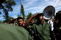 Members of the former Hatian military, which was demobilized in the mid 1990s, march with civilians.