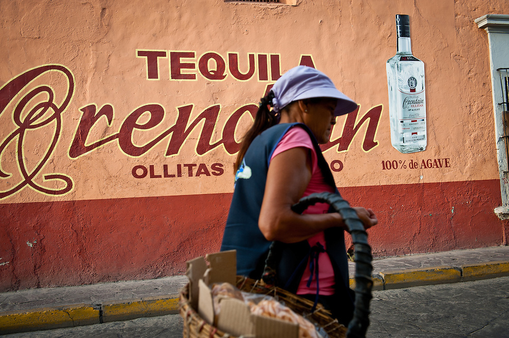 A street vendor walks past an advertisement for Tequila Orendain in the town of Tequila.