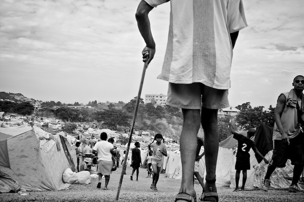 A man with a cane walks down one of the steep main paths in a camp for those displaced by the recent earthquake in Petionville, outside Port-au-Prince, Haiti.