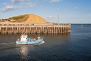 Small fishing boat leaving the harbour at West Bay, Bridport, Dorset, England, UK