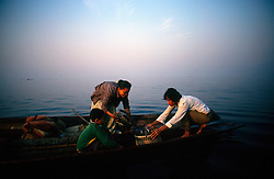 BURMA INLE LAKE MAR95 - A woman and her son meet with her husband fisherman to deliver his fish in the middle of Inle Lake. She will then transport it to a 'floating market', where the fresh catch is bartered for other goods. .. jre/Photo by Jiri Rezac. . © Jiri Rezac 1995. . Contact: +44 (0) 7050 110 417. Mobile: +44 (0) 7801 337 683. Office: +44 (0) 20 8968 9635. . Email: jiri@jirirezac.com. Web: www.jirirezac.com