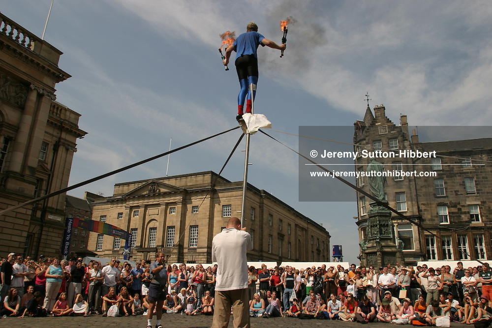 "A performer prepares to entertain the crowds, during the annual International Arts Festival, with his juggling and balancing skills, on the street known as the ""Royal Mile"", Edinburgh.."
